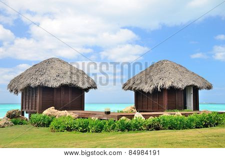 Two bungalows In Front Of Turquoise Sea.