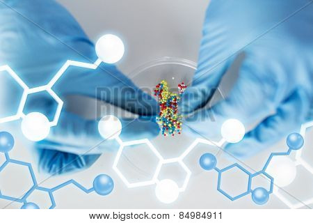 science, chemistry, biology, medicine and people concept - close up of scientist or doctor hands holding and pouring pill content into petri dish in laboratory with molecular structure