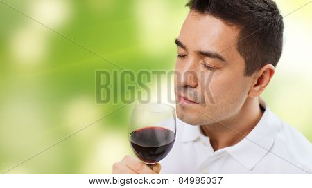 profession, drinks, leisure and people concept - happy man drinking and smelling red wine from glass over green background