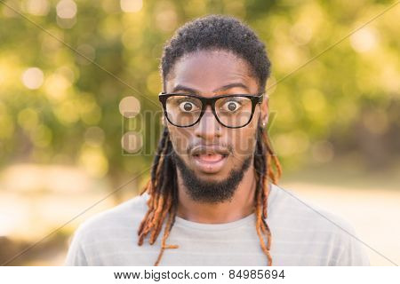 Handsome hipster looking surprised in park on a sunny day