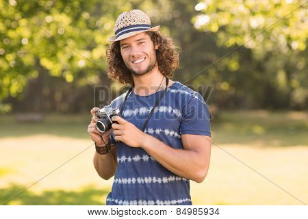 Handsome hipster using vintage camera on a sunny day