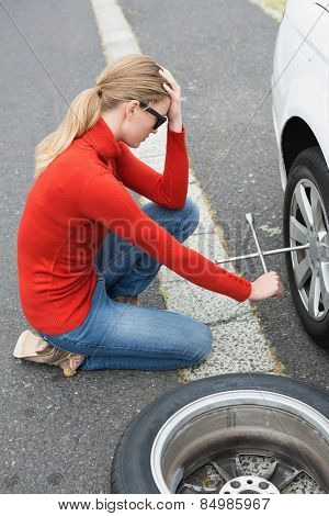 Annoyed woman trying to replace tire of her car