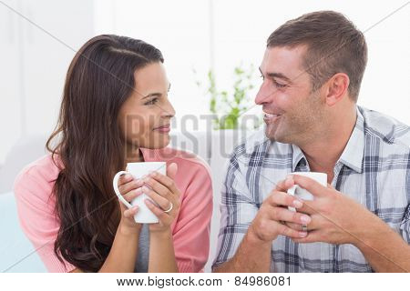 Happy couple looking at each other while having coffee at home