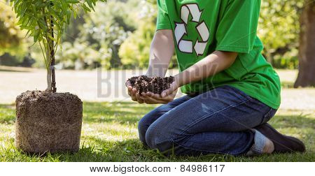 Environmental activist about to plant tree on a sunny day