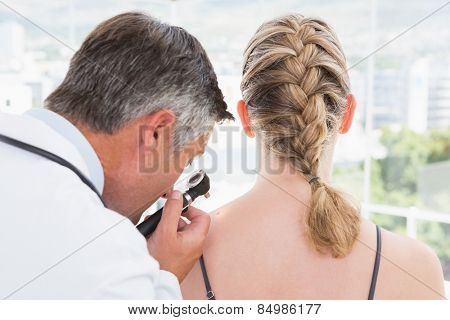 Doctor examining a spot at his patient in medical office