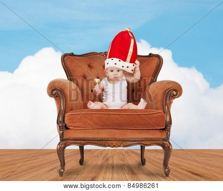 people, childhood and royalty concept - happy baby boy in royal hat with lollipop sitting on chair over blue sky and cloud background