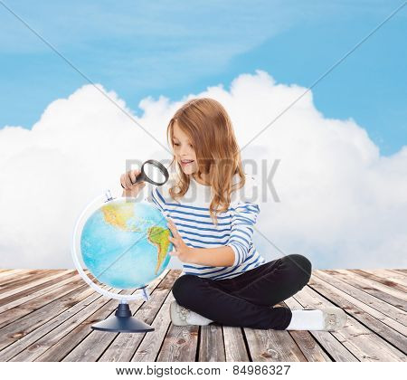 education, travel, childhood, geography and school concept - happy little student girl looking at globe with magnifier over blue sky and cloud background