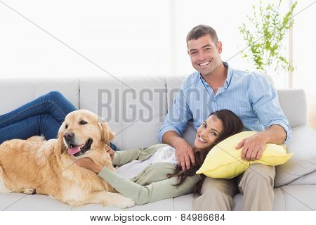 Portrait of happy couple with dog relaxing on sofa at home
