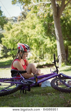 Injured woman after bike accident on a sunny day