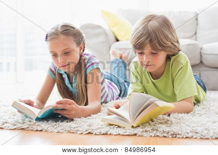 Siblings reading books while lying on rug in living room