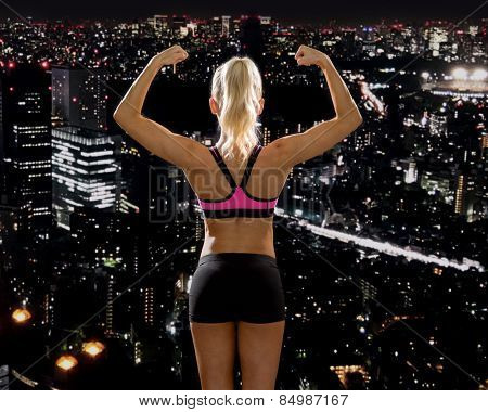 fitness, sport and diet concept - sporty woman from the back flexing her biceps