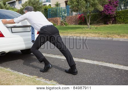 Man pushing his broken down car on the road