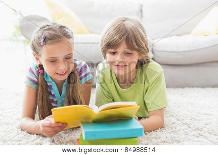 Siblings reading book while lying on rug in living room