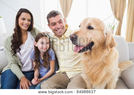 Happy family sitting with Golden Retriever on sofa at home