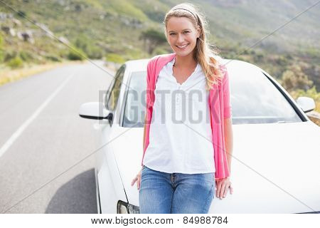 Pretty blonde leaning on the bonnet of her car
