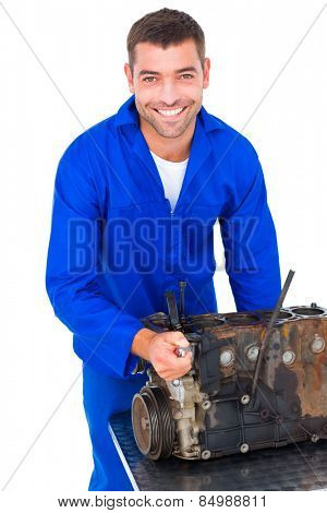 Portrait of smiling male machanic repairing car engine on white background