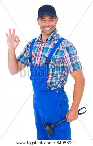 Portrait of happy plumber with plunger gesturing okay on white background