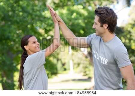 Happy volunteer couple high fiving on a sunny day