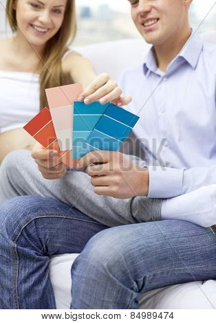 pregnancy, family, repair, decoration and people concept - close up of pregnant woman and man with color palettes at home