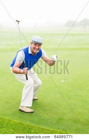 Happy golfer cheering on putting green on a foggy day at the golf course