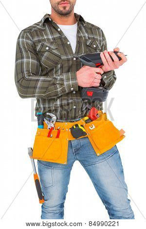 Manual worker holding gloves and hammer power drill on white background
