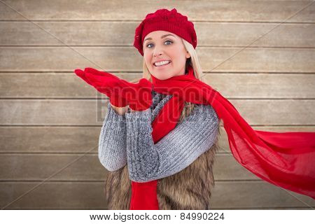 Blonde in winter clothes with hands out against wooden surface with planks