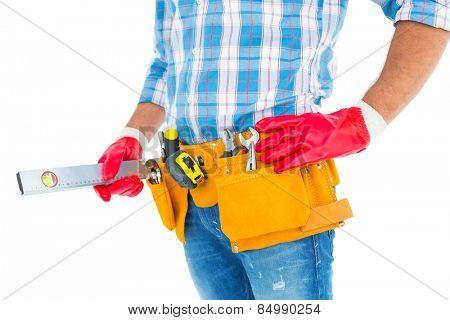 Midsection of handyman holding spirit level on white background