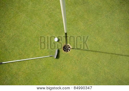 Golf club and golf ball on the putting green beside flag on a sunny day