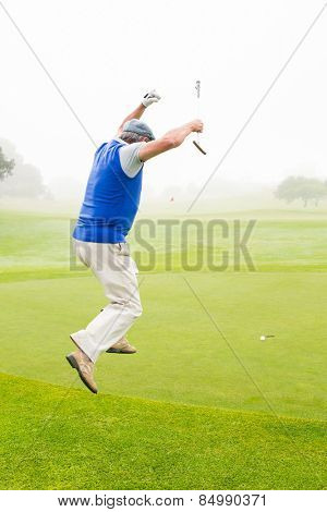 Excited golfer jumping up on a foggy day at the golf course