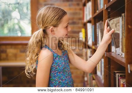 Cute little girl selecting book in library