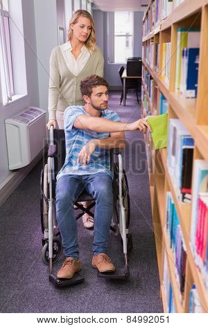 Smiling disabled student with classmate in library at the university