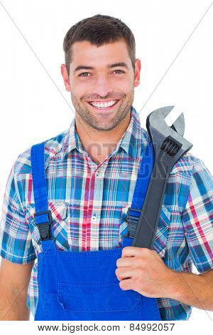 Portrait of confident male repairman holding adjustable wrench on white background