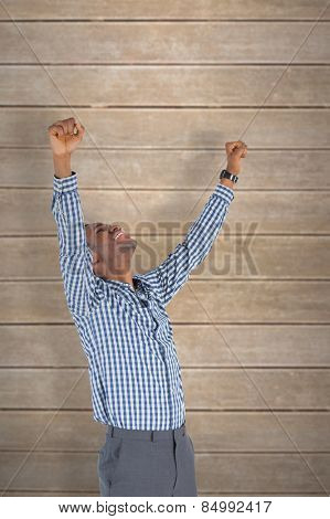 Excited businessman cheering against wooden planks