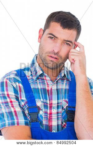 Portrait of confused manual worker scratching head on white background