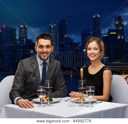 people, celebration, romantic and holidays concept - smiling couple eating main course with red wine at restaurant over night city background