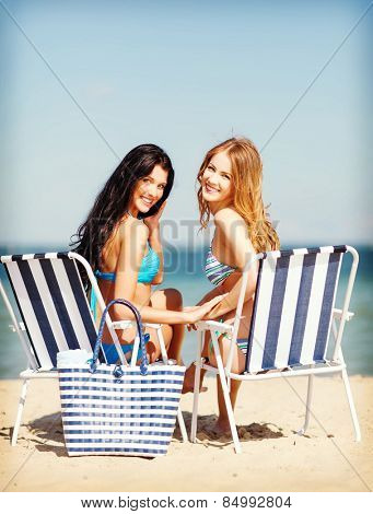 summer holidays and vacation - girls in bikinis sunbathing on the beach chairs