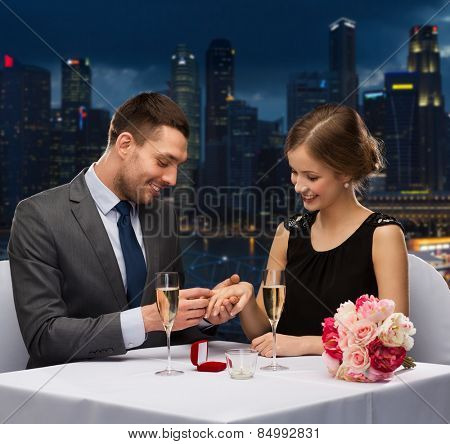 celebration, holidays and people concept - smiling couple with red gift box and wedding ring at restaurant over night city background