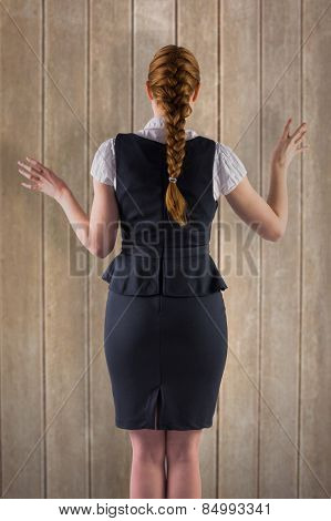 Redhead businesswoman with hands out against wooden surface with planks