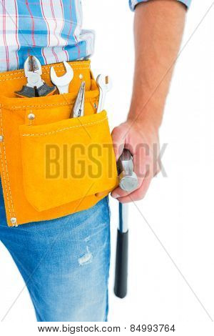 Midsection of handyman wearing tool belt while holding hammer on white background