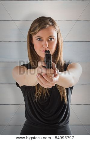 Femme fatale pointing gun at camera against wooden planks