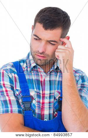 Confused manual worker looking down on white background