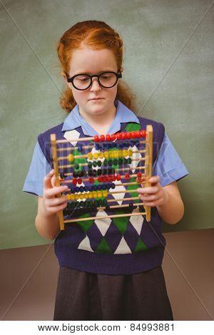 Portrait of cute little girl holding abacus in front of blackboard