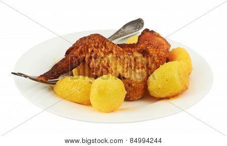 Chicken leg with potatoes in a plate