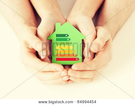 energy saving, real estate and family home concept - closeup of couple hands holding green paper house with energy efficiency rating