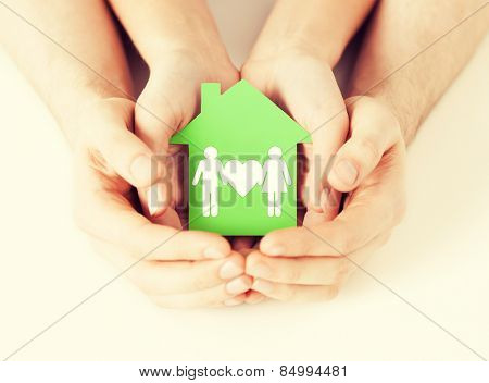 real estate and family home concept - closeup picture of male and female hands holding green paper house with family
