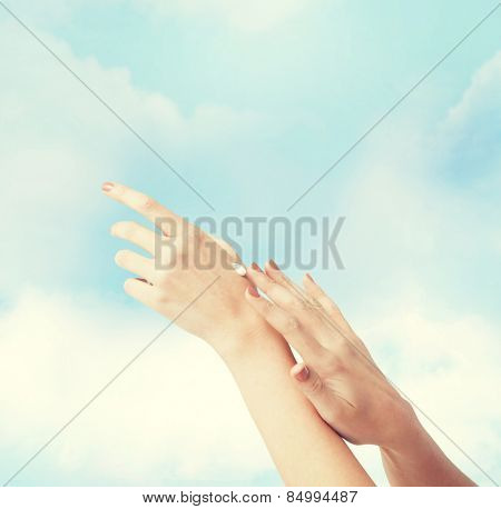 body parts, cosmetics and spa concept - close up of female soft skin hands with creme