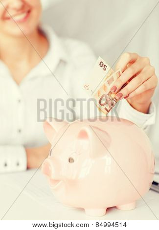 business, office, household, school, tax and education concept - woman puts euro cash into large piggy bank