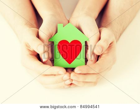 charity, real estate and family home concept - closeup picture of male and female hands holding green paper house with red heart