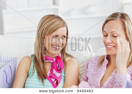 Two Charming Women Talking Together On The Sofa