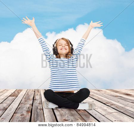 music, childhood, people and technology concept - happy girl with headphones listening to music over blue sky and cloud background